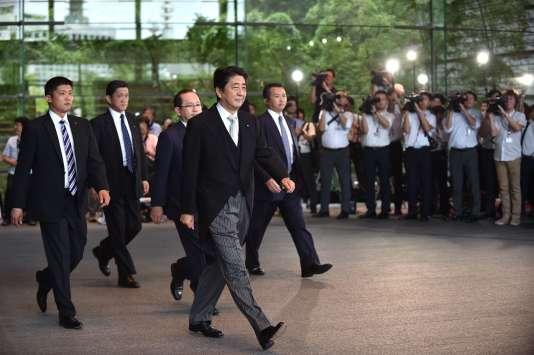 Le premier ministre japonais, Shinzo Abe (au centre), quitte sa résidence officielle pour se rendre au palais impérial, le 3 août, à Tokyo.