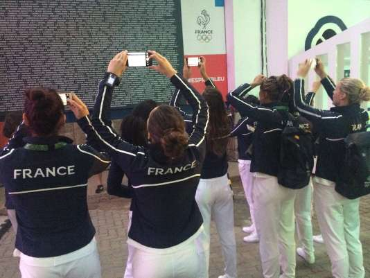 Les handballeuses photographient le panneau où figurent les noms des 394 sportifs de la délégation tricolore.