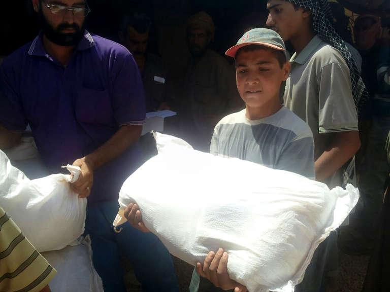 Un garçon transporte un sac d'aide dans le camp deréfugiés de Ruqban, en Jordanie.