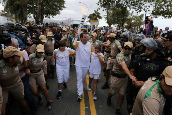 Le maire de Rio, Eduardo Paes, porte la flamme olympique sous bonne escorte, le 3 août 2016.