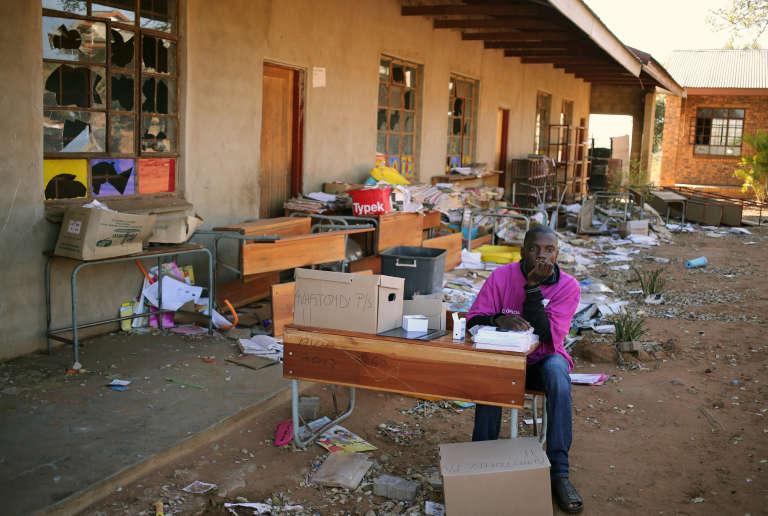 Un jeune homme attend les voteurs dans une école qui a été endommagée le 3 août à Vuwani en Afrique du Sud.