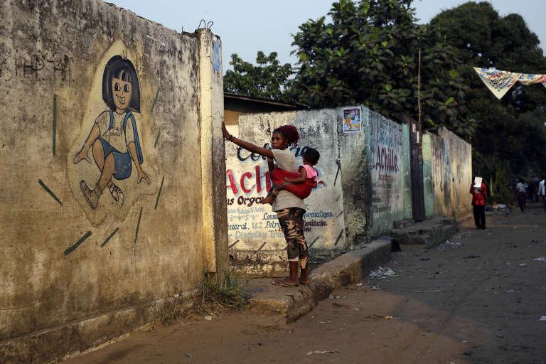 Une femme porte un enfant près d'une crèche du quartier Kisenso à Kinshasa (RD Congo), le 20 juin 2016.