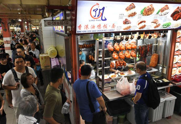 Des clients font la queue devant le stand Hong Kong Soya Sauce Chicken Rice & Noodle à Singapour, le 22 juillet 2016. AFP PHOTO / ROSLAN RAHMAN