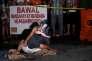 Jennilyn Olayres étreint le corps de Michael Siaron, tué à Manille, le 23 juillet. Sur le carton au sol : « Je suis un dealer ».