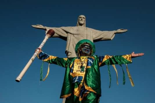 Un homme pose devant le Christ rédempteur, sur le Corcovado, à Rio, le 5août.