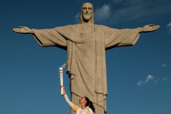 Maria Isabel Barroso Salgado, l'ancienne joueusede volley-ball brésilienne, porte la flamme olympique au pied de la statue du Christ, au sommet du Corcovado, à Rio de Janeiro, vendredi 5 août.