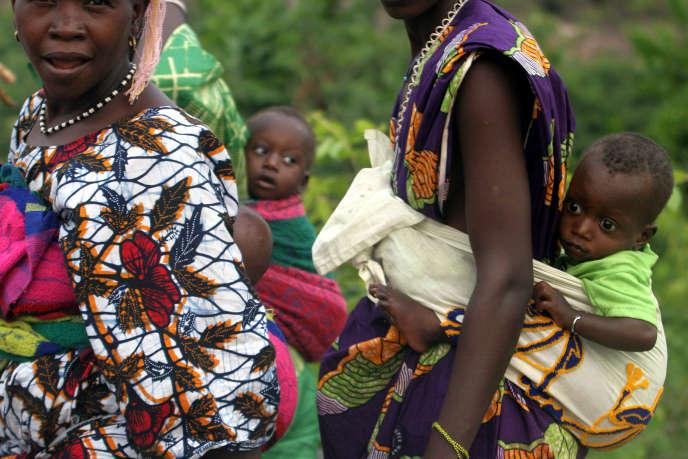 Des mères portent leurs enfants sur le dos.