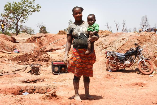 Adiata a fait 350 km pour trouver de l'or dans cette mine. Ici elle pose avec son fils de 4 mois, Mohamed, qui l'accompagne dans les carrières.