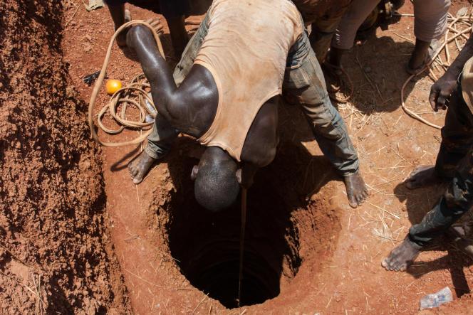 Un homme descend un seau dans un boyau de la mine aurifère de Kintinian en Guinée. 7 mètres plus bas, son collègue le chargera de pierres et de boue.