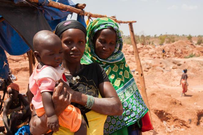 Après s'être essuyé le visage pour enlever la poussière irritante de la mine,Kadia pose avec son enfant et sa mère, Abou Berete.