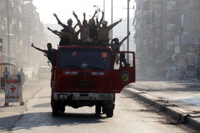 Des volontaires de la défense civile syrienne célèbrent la rupture du siège imposédepuis 3 semaines à la ville d'Alep, le 6 août 2016.