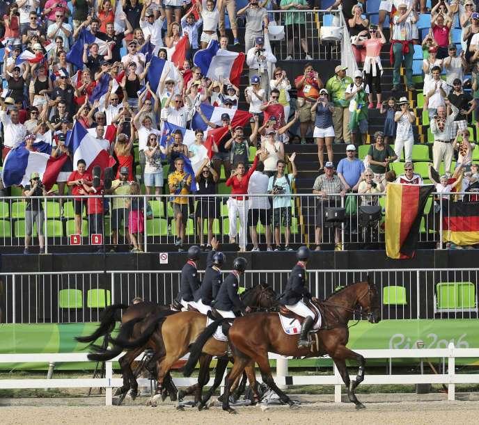 Astier Nicolas, Karim Laghouag, Thibaut Vallette et Mathieu Lemoine célèbrent leur médaille d'or au concours complet par équipes avec le public, mardi 9 août, à Rio.