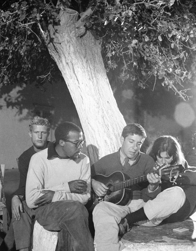Leonard Cohen, alors jeune poète de 25 ans, et sa guitare dans sa maison d'Hydra (Grèce) en octobre 1960. Marianne Ihlen est à sa droite.