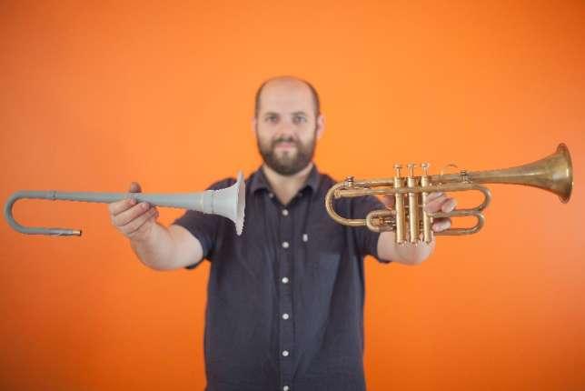 Jerôme Wiss présente, à gauche, une pièce imprimée en 3D qui a servi à prototyper la trompette finale, à droite.