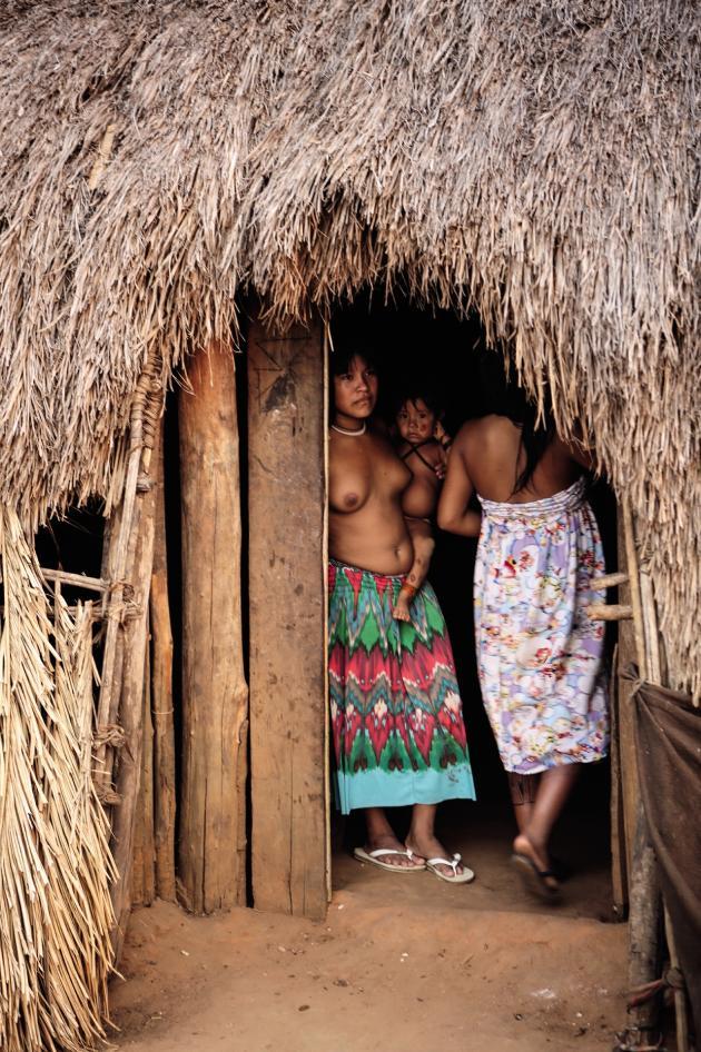 Femmes et enfants se protègent de la chaleur dans l'une des 24huttes de paille et de bois du village.