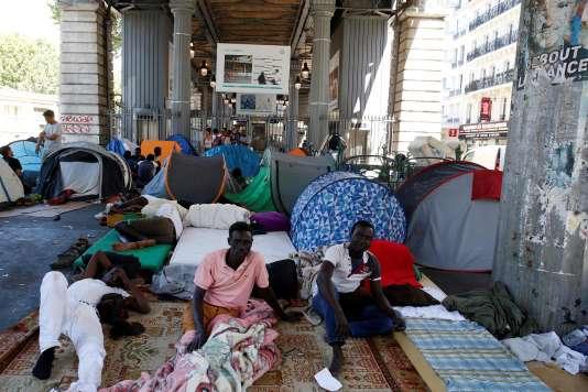 Des migrants dans un camp improvisé sous le métro aérien, à Paris, le 19 juillet 2016.
