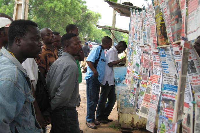 Des Togolais lisant les titres de presse, dans les rues de Lomé, au Togo.