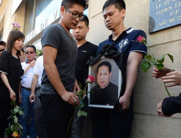 Des membres de la famille de Chaolin Zhang montrant sa photo, le 14 août 2016, à Aubervilliers.