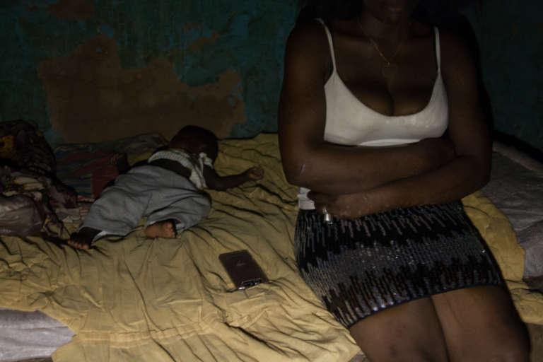 Evelyne assise auprès de Maïga. Il fait chaud, elle chasse les moustiques d'un revers de main.