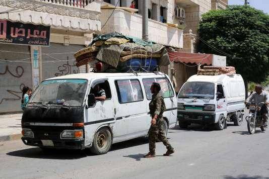Un membre des Forces démocratiques syriennes contrôle des habitants rentrant à Manbij, le 14août.