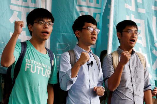 De gauche à droite, le 15 août 2016, les dirigeants étudiants Joshua Wong, Nathan Law et Alex Chow lancent des slogans avant le prononcé du verdict, dans un procès où ils sont accusés d'incitation et de participation à un rassemblement illégal, lors du « mouvement des parapluies» en 2014.