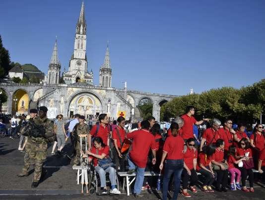 Fidèles sous la protection de militaires au sanctuaire de Notre-Dame de Lourdes, le 15 août.