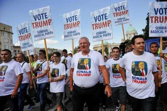 Des membres du Parti radical serbe (ultranationaliste) défilent devant le Parlement serbe à Belgrade, mardi 16 août, pour protester contre la visite du vice-président américain, Joe Biden. Au centre, leur chef, Vojislav Seselj, entouré de militants portant des pancartes appelant à voter pour le candidat républicain, Donald Trump.