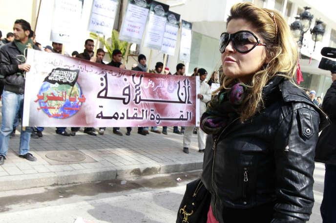 Une passante devant des partisans de Hizb Ut-Tahrir, lors d'une manifestation en face de l'amabassade de Franec à Tunis, le 14février 2013.