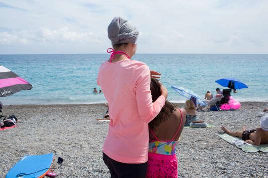 Une jeune maman et sa fille sur la plage de Nice. Elle explique que lorsqu'elle se baigne, elle se baigne dans cette tenue, une version contemporaine: leggins, tee-shirt et voile noué sur la tête.