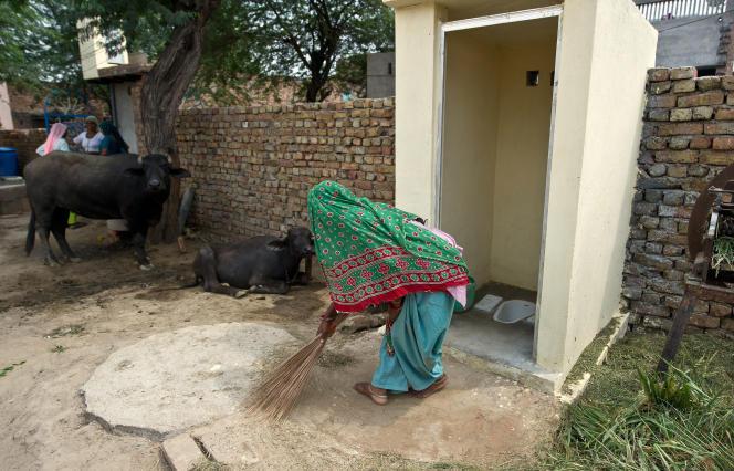 Une villageoise balaie devant des toilettes neuves installées dans le village d'Hirmathala (Etat de l'Haryana) en août 2014.