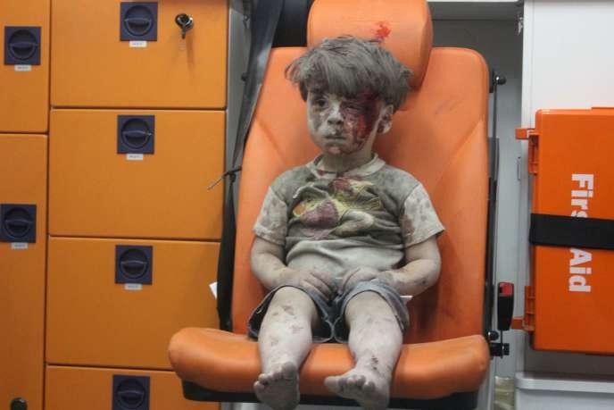 Omrane, petit garçon syrien d'environ 4 ans, recouvert de poussière et de sang après avoir été secouru des décombres d'un bâtiment touché par un raid aérien à Alep, le 17 août.