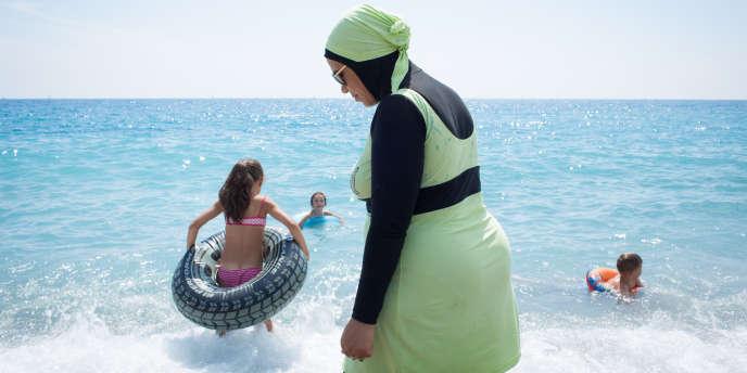 Une jeune maman portant une combinaison intégrale pour se baigner à Nice le 17 juillet 2016.