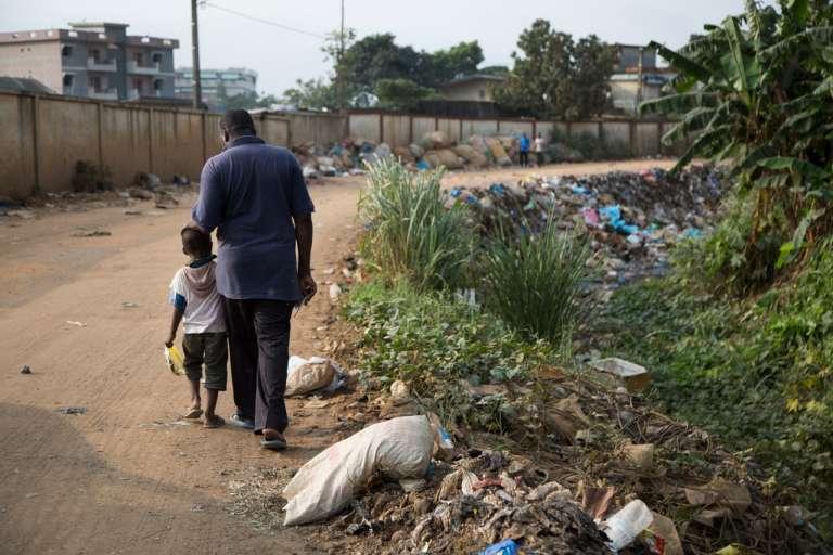 Moustapha Sangaré, ancien travailleur à la décharge d'Akouédo et son fils, au bord du caniveau où a été déversée une partie des déchets du «Probo-Koala».