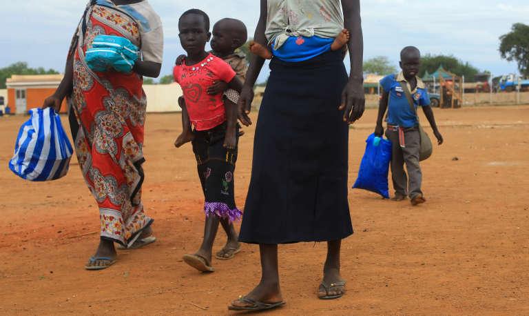 Une famille de réfugiés arrive dans un camp du Haut commissariat de l'ONU pour les réfugiés (HCR) à Elegu, dans le nord de l'Ouganda, non loin de la frontière avec le Soudan du Sud, le 20 août 2016.