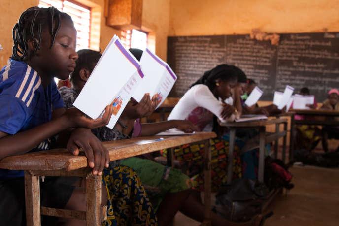 Studieuses, les élèves lisent la brochure de sensibilisation aux menstruations.