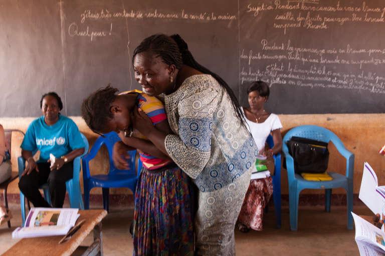 L'institutriceDjamila Dayamba félicite une fille qui a répondu correctement à ses questions.