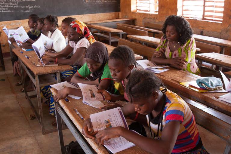 De jeunes élèves burkinabées lisent à haute voix des extraits de la brochure de sensibilisation aux menstruations.