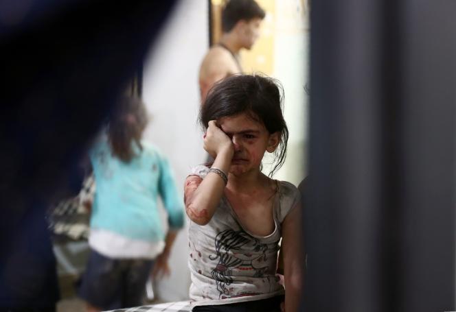 Une petite fille blessée attend à l'hôpital après une frappe aérienne sur le quartier de Douma, tenu par les rebelles, à Damas, le 23 août.