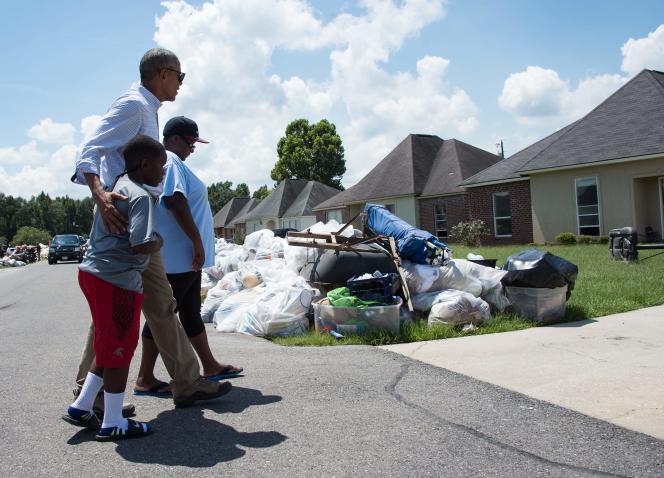 Le président américain, Barack Obama, le 23 août, avec deux habitants de Bâton-Rouge touchés par les inondations.
