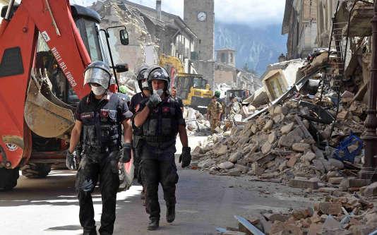 Des équipes de secours à Amatrice. En arrière-plan, le campanile de l'église Saint-Augustin, le 24 août.