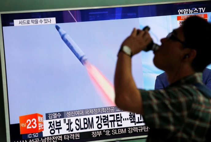 En Corée du Sud, à Séoul, un piéton passe devant un écran de télévision diffusant un reportage sur le tir de missile balistique au large de Sinpo, sur la côte orientale de Corée du Nord, le 24 août 2016.