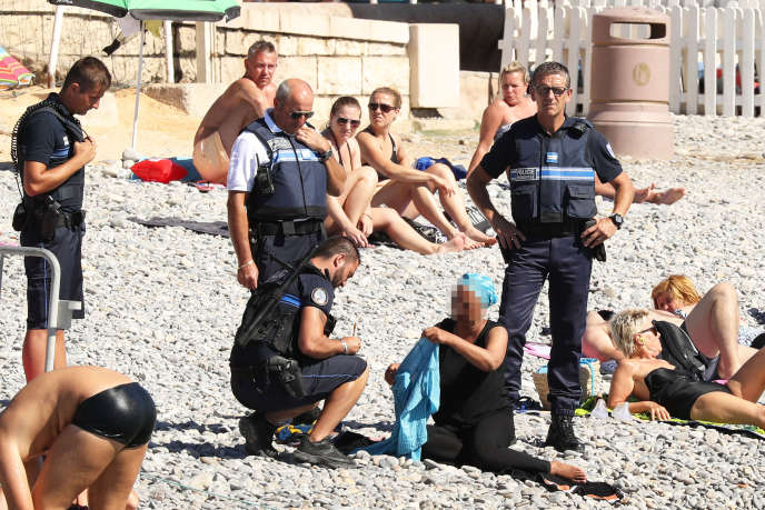 Une femme vêtue d'une tunique et d'un turban bleu est contrôlée et se voit infliger une amende sur la plage de la promenade des Anglais, à Nice, le 23 août.