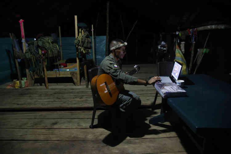 Manuel, un sous-commandant FARC du 48e front, apprend à jouer de la guitare sur Internet.