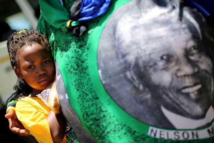 Une jeune fille regarde un pagne avec la photo de Mandela, lors du congrès de l'ANC, en janvier 2016.