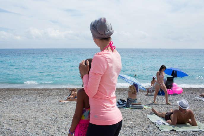Une jeune maman et sa fille sur la plage de Nice.
