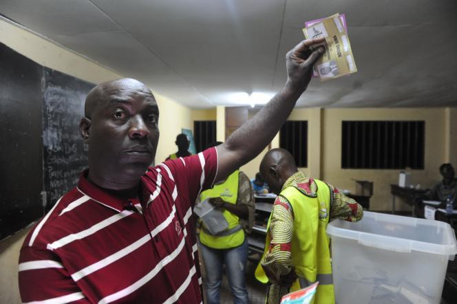 Un homme montre un bulletin de vote lors d'un comptage électoral, à Libreville, le 27 août.