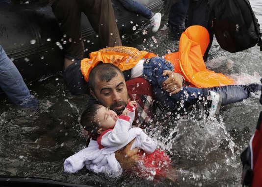 Un Syrien avec ses deux enfants tentant de débarquer après la traversée depuis la Turquie. Île de Lesbos, 24 septembre 2015.