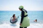Une jeune maman portant une combinaison intégrale pour se baigner. Ici, avec sa fille. Cette tenue, bien que très courante dans des pays comme la Malaisie ou l'Indonesie est très marginale en France. A Nice, en ce 17 juillet 2016, elle est la seule à la porter, sans que cela ne crée de gêne, ni pour elle, ni pour son entourage.