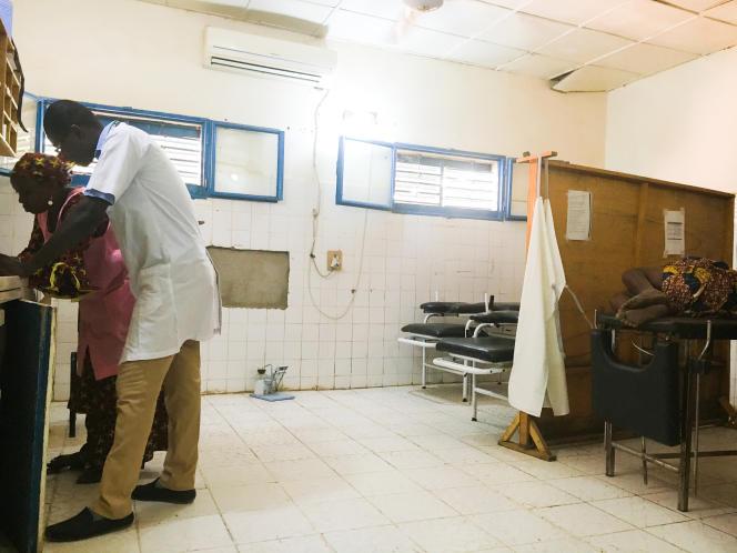 En attendant le résultat des analyses sanguines de Madina Ada, enceinte de son onzième enfant, un médecin et une infirmière consultent son carnet de soins.