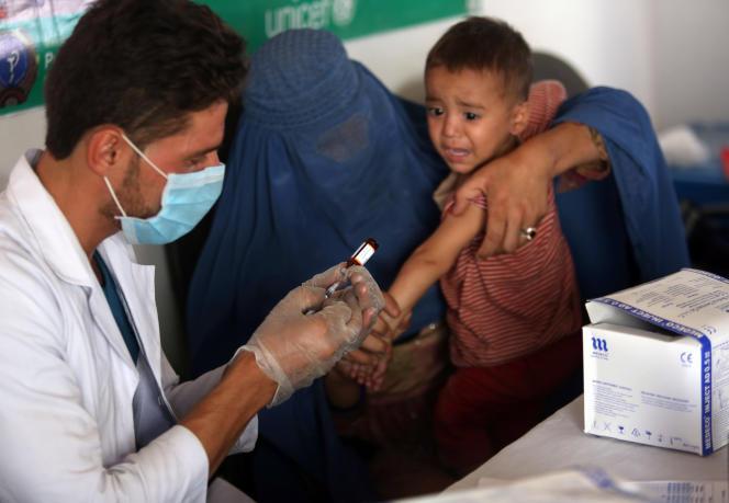 Un enfant afghan se fait vacciner après être récemment arrivé au centre d'enregistrement du Haut-Commissariat pour les réfugiés des Nations unies à Kaboul.Rahmat Gul / AP